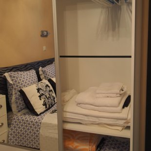 The floor - to - ceiling closet with mirrored doors in the bedroom has plenty of space.