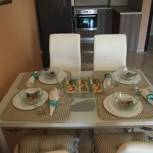 The glass top table and eco-leather chairs are comfortable and easy to maintain.