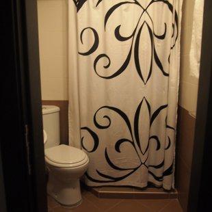 Тhe bathroom is tiled floor to ceiling.