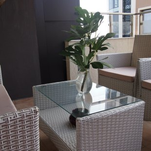 The terrace has weather resistant rattan furniture.