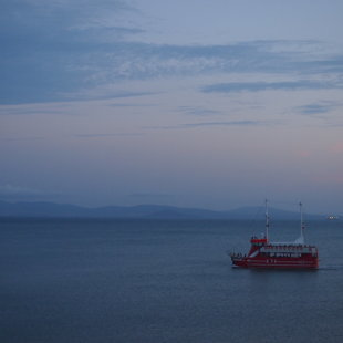 Една от лодките за разходка из залива по  своя  път обратно към кея.